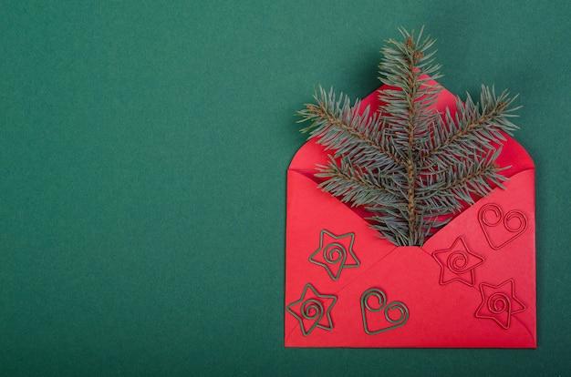 Weihnachtsbaumzweig in einem roten umschlag, auf einem grünen hintergrund. neujahrsdekoration.