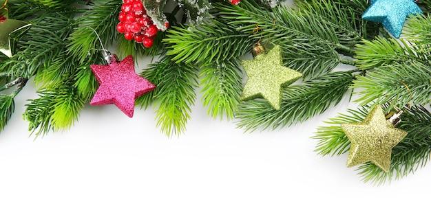 Weihnachtsbaumzweig mit roten beeren und dekorationen auf weißem hintergrund