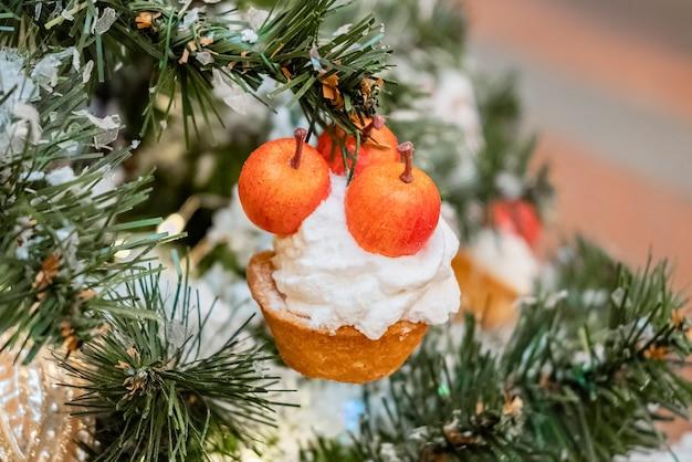 Weihnachtsbaumzweig verziert mit kirschkuchenverzierung
