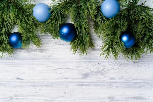 Weihnachtsbaumzweige auf weißem hölzernem hintergrund mit kopienraum