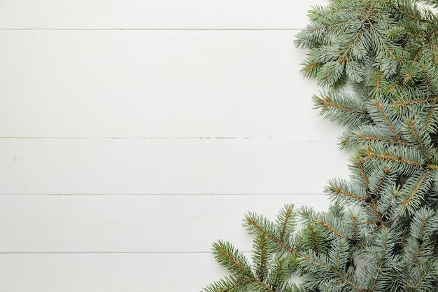 Weihnachtsbaumzweige auf weißer holzoberfläche