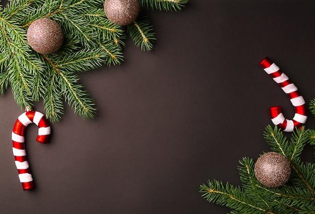 Weihnachtsbaumzweige mit goldkugeln und zuckerstange im schwarzen hintergrund