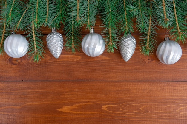 Weihnachtsbaumzweige mit neujahrsspielzeug auf hölzernem hintergrund