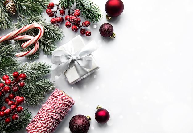 Weihnachtsbaumzweige mit roten kugeln auf weißem hintergrund. rand, draufsicht, flach liegen