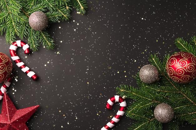 Weihnachtsbaumzweige mit roten und goldenen kugeln und zuckerstange auf schwarzem hintergrund mit schnee in der draufsicht