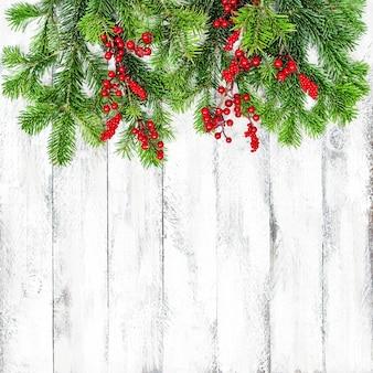 Weihnachtsbaumzweige mit roter beerendekoration auf hölzernem hintergrund