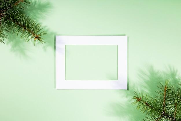 Weihnachtsbaumzweige mit schatten, weißer rahmen
