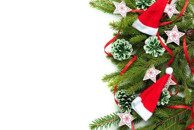 Weihnachtsbaumzweige mit zapfen und kappen werden auf einen weißen hintergrund gelegt.