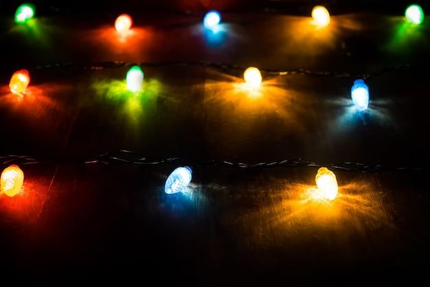 Weihnachtsbeleuchtung auf holztisch. farbige lichter auf einer weihnachtsgirlande in der dunkelheit der nacht