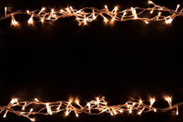 Weihnachtsbeleuchtung grenze. weihnachtshintergrund mit lichtern, weihnachtslichter auf schwarzem hintergrund. neujahr.