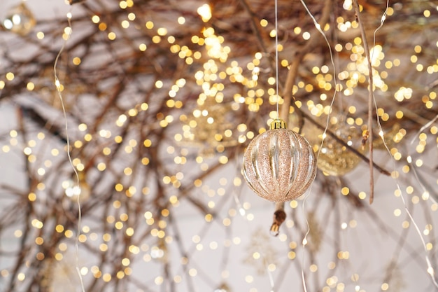 Weihnachtsbeleuchtung und ball über ästen von einem baum und lichtern