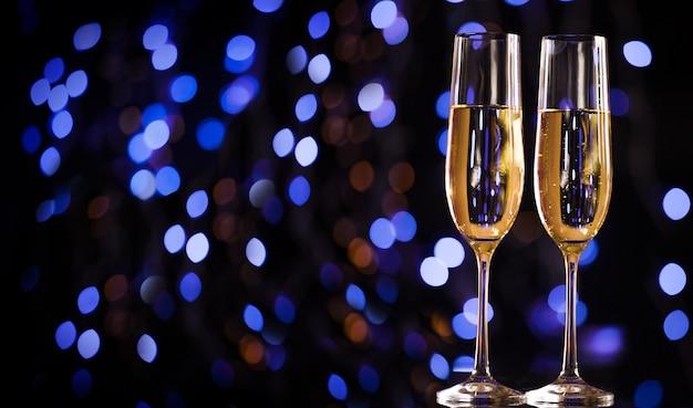 Weihnachtsbeleuchtung und champagnerglas. frohes neues jahr. hintergrund der weihnachts- und neujahrsfeiertage