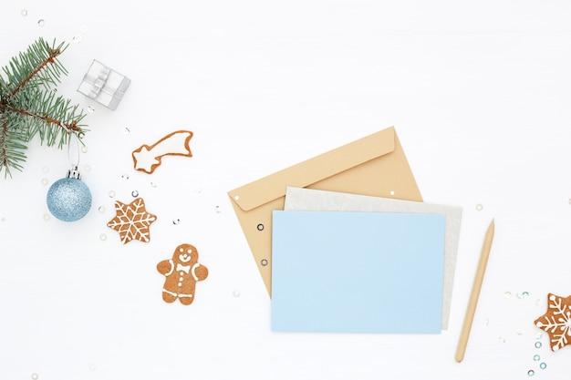 Weihnachtsblaue leere karte, umschlag, lebkuchen und neujahrsdekorationen auf weißem tisch