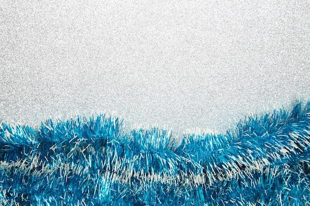 Weihnachtsblaues lametta auf silbernem glitzerndem hintergrund.