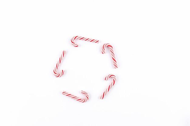 Weihnachtsbonbon-karamell-zuckerstange auf weißem weihnachtsfeiertagskonzept vorlage der grußkarte