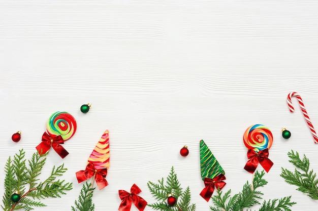 Weihnachtsbonbons sortierte draufsicht grüne thujazweige kleine rote und grüne ballspielzeuge