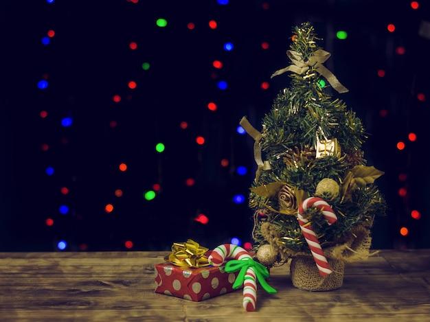 Weihnachtsbonbons und -geschenke auf einem holztisch nahe einem tannenbaum.