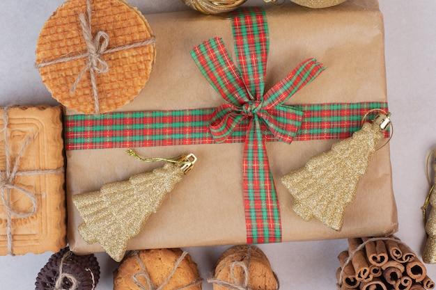 Weihnachtsbox mit keksen, waffeln und zimtstangen im seil