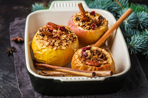Weihnachtsbratäpfel mit granola, moosbeeren, nüssen und honig im ofenteller, dunkler hintergrund.