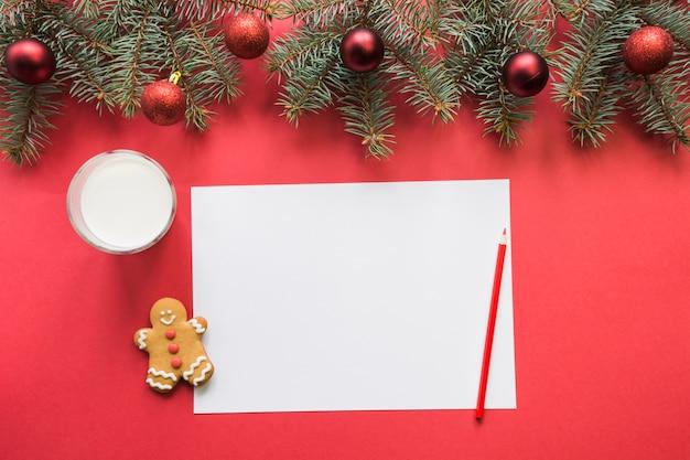 Weihnachtsbrief für santa claus mit milch, plätzchen, lebkuchen auf rot. draufsicht und platz für ihren text. flach liegen.