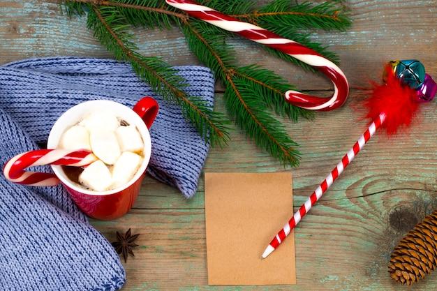 Weihnachtsbriefschreiben auf papier auf hölzernem hintergrund mit dekorationen.