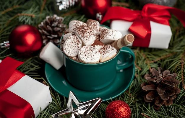 Weihnachtscappuccino mit marshmallows in einem grünen becher, tannenzweigen, weihnachtsspielzeug