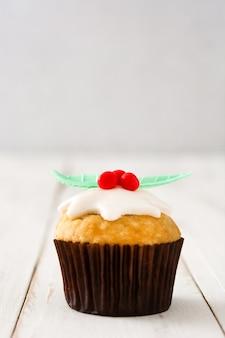 Weihnachtscupcake auf weißem holztisch