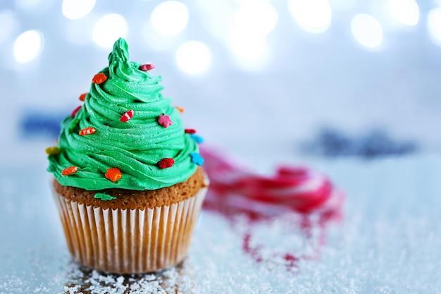 Weihnachtscupcake mit lichtern im hintergrund