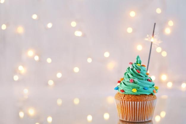 Weihnachtscupcake mit wunderkerze und lichtern im hintergrund