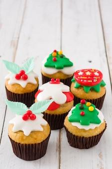 Weihnachtscupcakes auf weißem holztisch