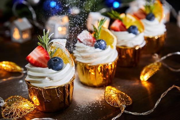 Weihnachtscupcakes dekoriert mit frischen blaubeeren und erdbeeren