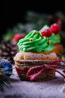Weihnachtscupcakes in einem festlichen und verschneiten wald. dessert für silvester und weihnachtsfeier.