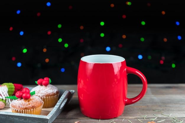 Weihnachtscupcakes verziert mit mistel mit einer roten tasse tee