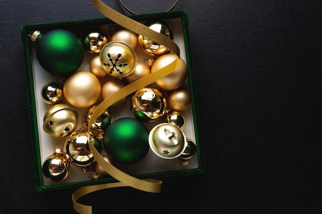 Weihnachtsdeko-box mit kugeln auf dunklem hintergrund. flache lage. weihnachtskonzept