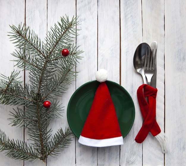 Weihnachtsdeko mit rotem hut auf weißem hintergrund mit tannenzweig