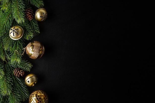 Weihnachtsdeko mit tanne und kugeln auf dunkelheit.