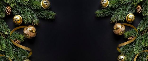Weihnachtsdeko mit tanne und kugeln auf dunklem hintergrund. flache lage. weihnachtskonzept. horizontal