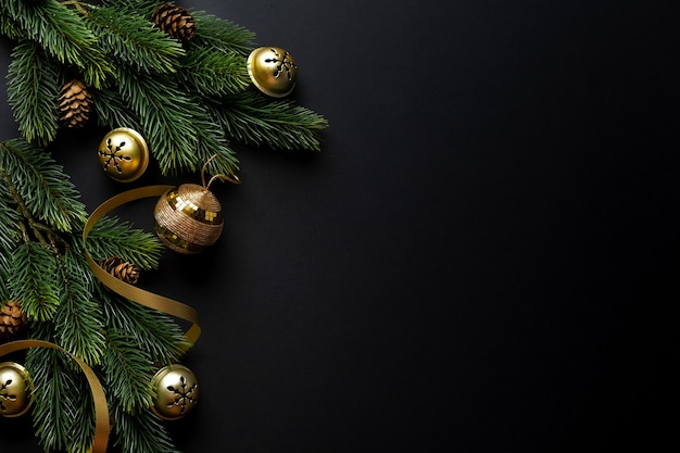 Weihnachtsdeko mit tanne und kugeln auf dunklem hintergrund. flache lage. weihnachtskonzept
