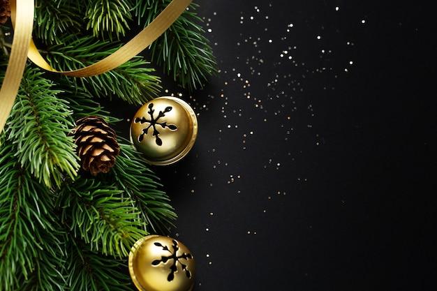 Weihnachtsdeko mit tanne und kugeln auf dunklem hintergrund. nahansicht. weihnachtskonzept