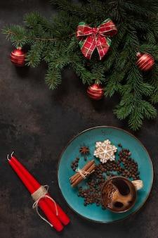 Weihnachtsdeko mit tannenzweigen, roten kerzen, lebkuchenplätzchen und kaffee mit zimtstangen