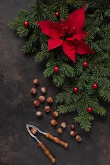 Weihnachtsdeko mit tannenzweigen, weihnachtsstern, haselnüssen und nussknacker
