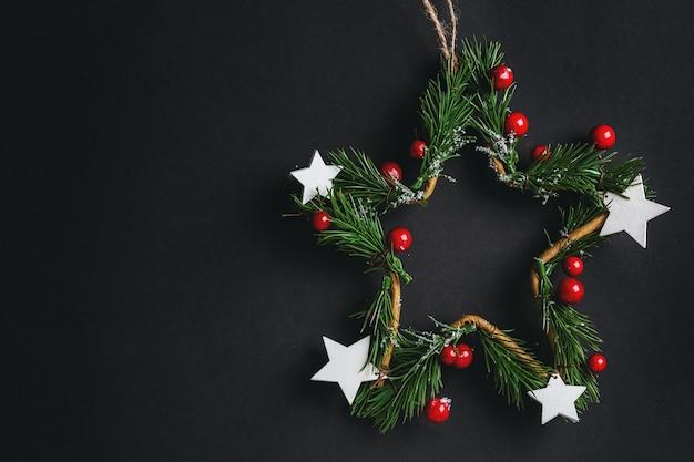 Weihnachtsdeko-sternkranz auf schwarz. flache lage.
