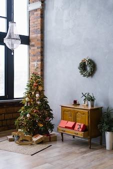 Weihnachtsdekor in der wohnzimmerdachbodenart mit großen fenstern, weihnachtsbaum im haus