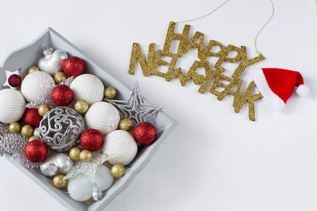 Weihnachtsdekor in einem grauen tablett: bälle, herzen, sterne und in goldenen buchstaben frohes neues jahr geschrieben