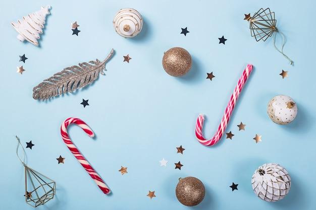 Weihnachtsdekor mit süßigkeitsessstäbchen auf einem hellen blauen hintergrund
