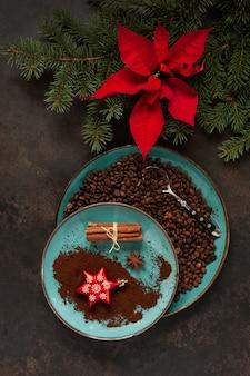 Weihnachtsdekor mit tannenzweigen, poinsettia und kaffeebohnen in einer platte mit zimtstangen