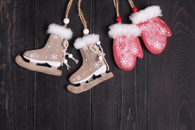 Weihnachtsdekor. schlittschuhe, handschuhe auf einer hölzernen hintergrundebene legen draufsicht