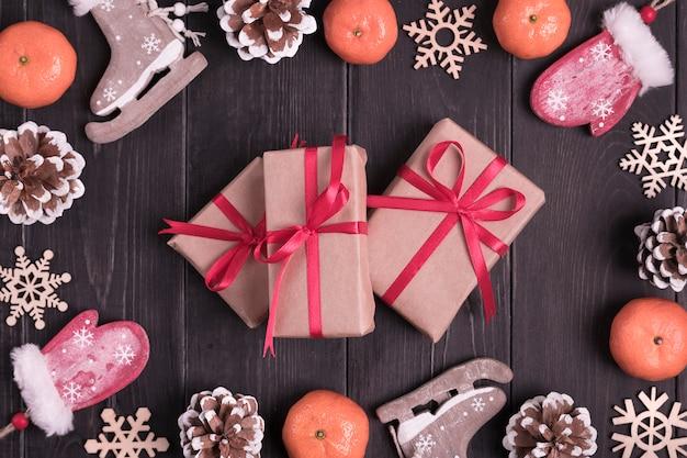 Weihnachtsdekor. schlittschuhe, handschuhe, schneeflocken, mandarinen, kegel, kasten auf hölzernen hintergrund legen flach