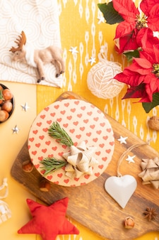 Weihnachtsdekoration auf dem tisch. flatlay mit bastelgeschenkbox, weihnachtsstern, nüssen, weihnachtsschmuck