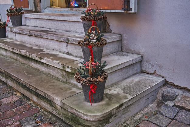 Weihnachtsdekoration auf der treppe des cafés. blecheimer mit tannenzapfen und zierbändern. straßenweihnachtsdekoration im urlaub
